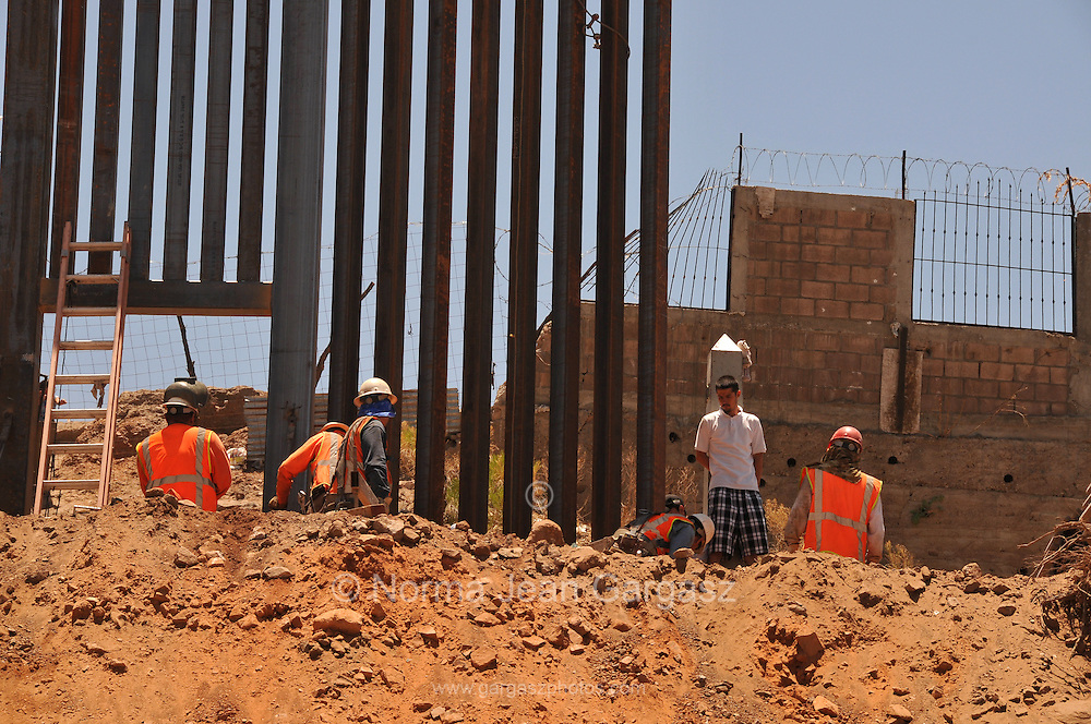 To increase security and visibility along the U.S./Mexico border workers replace a 2.8 mile section of landing matt border wall constructed in 1994 in Nogales, Arizona, USA.  The project costs $11.6 million.  Under tight security on the Arizona side of the border, the construction draws much interest from residents of Nogales, Sonora, Mexico.  The concrete marker originally designated the border.