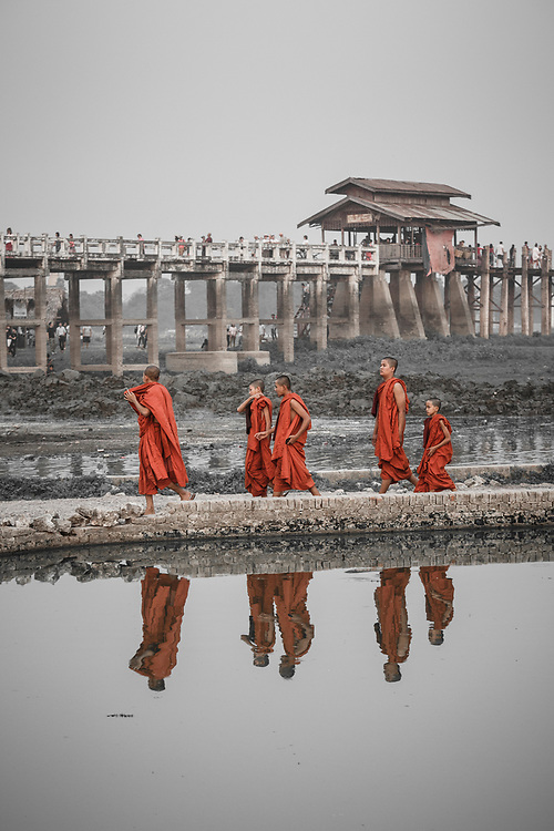 Monks walking home in the evening next to U Bein Bridge, a crossing that spans the Taungthaman Lake near Amarapura in Myanmar. The 1.2-kilometre bridge was built around 1850 and is believed to be the oldest and longest teakwood bridge in the world.