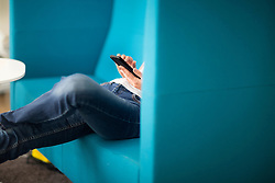 Mid section of a woman using smart phone in the office, Freiburg im Breisgau, Baden-W¸rttemberg, Germany