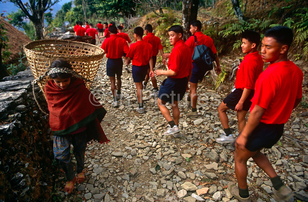 Young Nepali boys admire a young girl on an army walk along Himalayan path during recruitment to the Gurkha Regiment. Trying for places in the Gurkha Regiment is part of tough endurance series to find physically perfect specimens for British army infantry training. They will need to perform 25 straight-kneed sit-ups at a 45° slant both within 60 seconds to pass. 60,000 boys aged between 17-22 (or 25 for those educated enough to become clerks or communications specialists) report to designated recruiting stations in the hills each November, most living from altitudes ranging from 4,000-12,000 feet. After initial selection, 7,000 are accepted for further tests from which 700 are sent down here to Pokhara. Only 160 of the best boys succeed in the journey to the UK. The Gurkhas have been supplying youth for the British army since the Indian Mutiny of 1857.