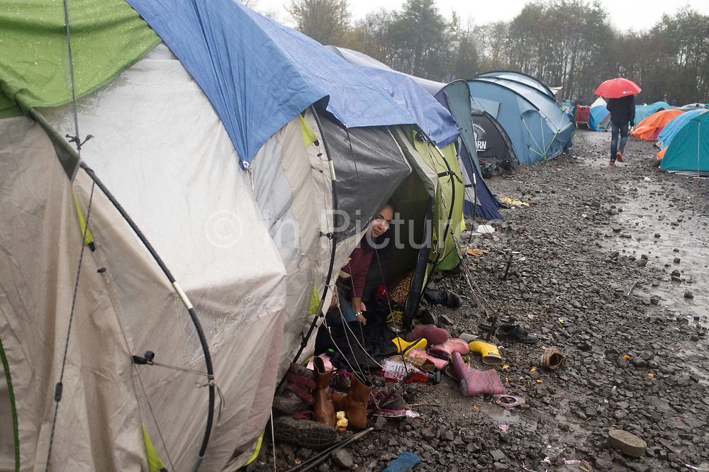 France. Refugees. Grande Synthe camp near Dunkirk. People are camping in a wood with very few facilities.  A child  from a Kurdish family from Iraq shelters in her tent from the pouring rain.