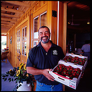 Le Terroir produce stand in the Eastern Townships of Quebec.  The owner holds fresh strawberries.