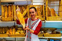Woman selling bread in the Panaderia Maria, Granada, Granada Province, Andalusia, Spain.