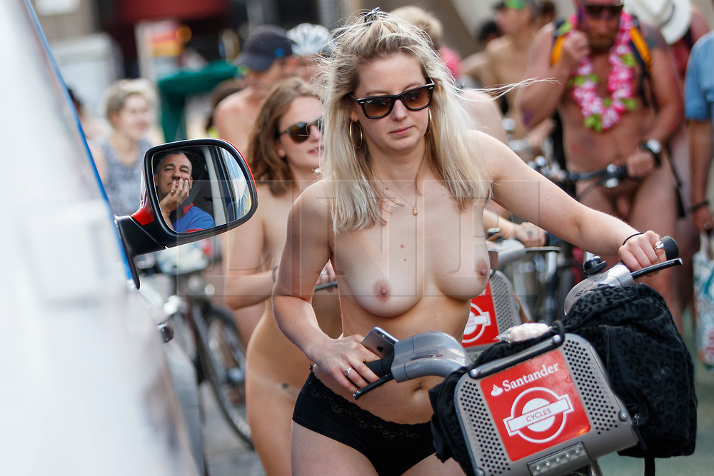 © Licensed to London News Pictures. 10/06/2017. London, UK. A man waiting on traffic watches nude protesters take part in a naked bike ride in central London on Saturday, 10 June 2017 as part of the World Naked Bike Ride event, which protests against car culture and aims to raise awareness of cyclists on the roads. Photo credit: Tolga Akmen/LNP