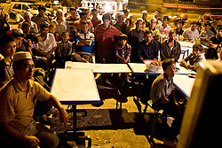 Uighr men watch television on the street in Hotan, Xinjian province in China.