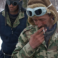 North of the Arctic Circle in Russia, nomadic Komi reindeer herders await arrival of the reindeer.  Their clothing and goggles come from time performing mandatory  Russian military service.