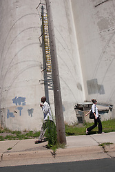 Two people walk in opposite directions in front of a vintage grain silo in Minneapolis