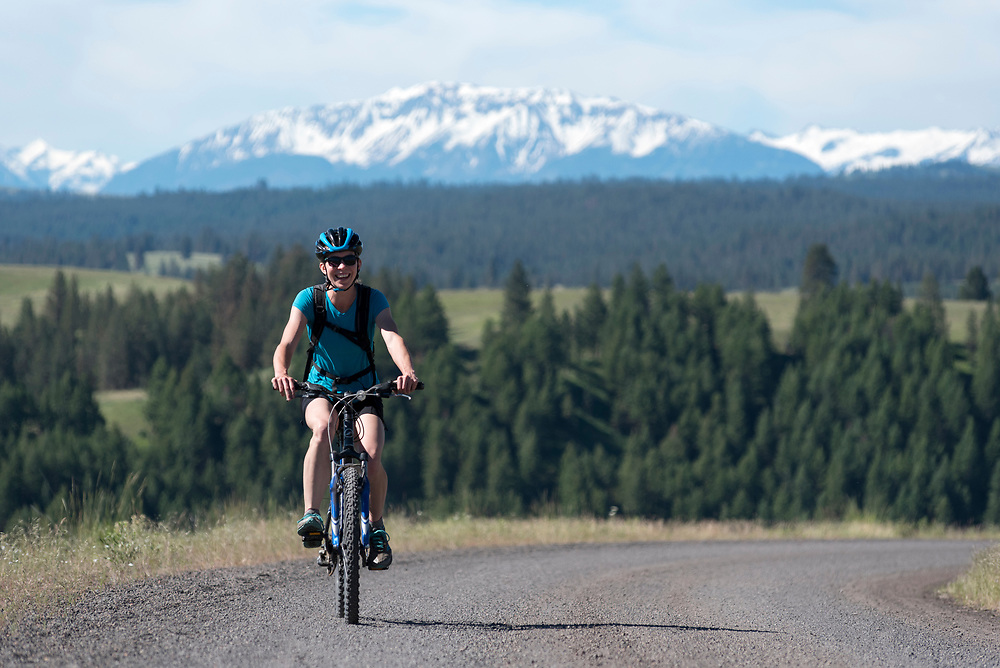 Woman mountain biking a road in Wallowa - Whitman National Forest, Oregon.