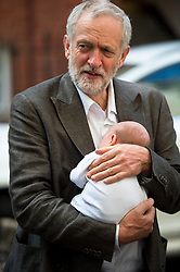 **FILE PICTURE - Monday December 21 marks 100 days since Jeremy Corbyn became leader of the Labour Party** ©  London News Pictures. 19/07/2015. London, UK. JERMY CORBYN holding 4 week old Faolán Murphy O'Donnell as he arrives at the venue. Labour leadership candidates Jeremy Corbyn, Yvette Cooper, Liz Kendall and Andy Burnham attend a hustings at the Camden Centre in London. The new leader is due to be announced in September 2015.  Photo credit: Ben Cawthra/LNP