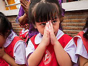 """23 JUNE 2015 - MAHACHAI, SAMUT SAKHON, THAILAND:  School children pray during the City Pillar Shrine Procession in Mahachai. The Chaopho Lak Mueang Procession (City Pillar Shrine Procession) is a religious festival that takes place in June in front of city hall in Mahachai. The """"Chaopho Lak Mueang"""" is  placed on a fishing boat and taken across the Tha Chin River from Talat Maha Chai to Tha Chalom in the area of Wat Suwannaram and then paraded through the community before returning to the temple in Mahachai.    PHOTO BY JACK KURTZ"""