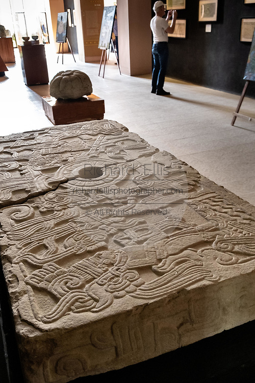 Mesoamerica carved stone tablet on display in the museum at the pre-Columbian archeological complex of El Tajin in Tajin, Veracruz, Mexico. El Tajín flourished from 600 to 1200 CE and during this time numerous temples, palaces, ballcourts, and pyramids were built by the Totonac people and is one of the largest and most important cities of the Classic era of Mesoamerica.