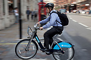 Man on a Cycle Hire scheme bike turns of Shaftesbury Avenue in central London. These Boris Bikes as they have become affectionately known are being widely used by local Londoners and tourists alike. Like this business man.