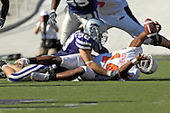 Oklahoma State quarterback Bobby Reid (14) reaches up and recovers the fumbled ball, after getting tackled by Kansas State defensive end Ian Campbell (98) in the first half, at Bill Snyder Family Stadium in Manhattan, Kansas, October 7, 2006.  The Wildcats beat the Cowboys 31-27.<br />