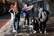 Chinese tourists stop to look at a map while trying to find their way around London, UK.