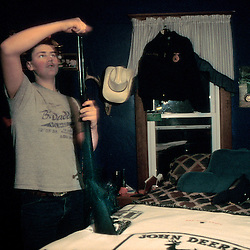 Levi, a future farmer of America, cleans his squirrel hunting gun, in his bedroom.  He surrounds himself with the accoutrement of a farm boy of yesteryear: a poster of a John Deere tractor, and matching counterpane.