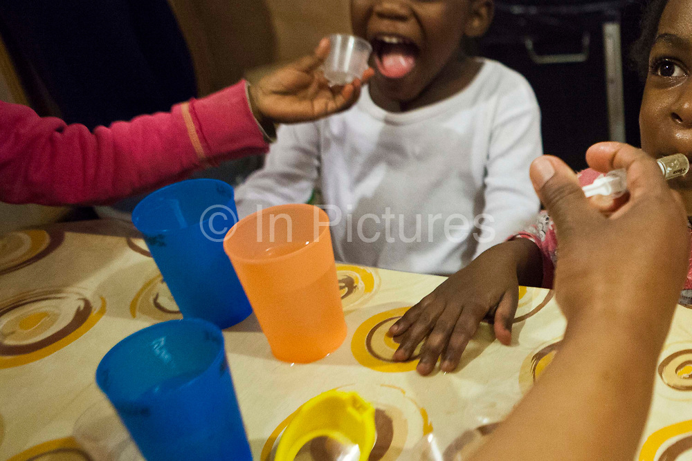 A nurse administers medicine to young African children.  One child swallows syrup from a syringe. The other has just taken tablets.  The children are living at Lambano Sanctuary, a hospice and care home for children with HIV/AIDS.  Guateng, South Africa.