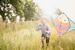 Little boy running with kite on meadow in countryside, Bavaria, Germany
