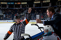 KELOWNA, CANADA - FEBRUARY 15: Referee Nick Panter stands at the bench and speaks to Kelowna Rockets' head coach Adam Foote against the Everett Silvertips  on February 15, 2019 at Prospera Place in Kelowna, British Columbia, Canada.  (Photo by Marissa Baecker/Shoot the Breeze)