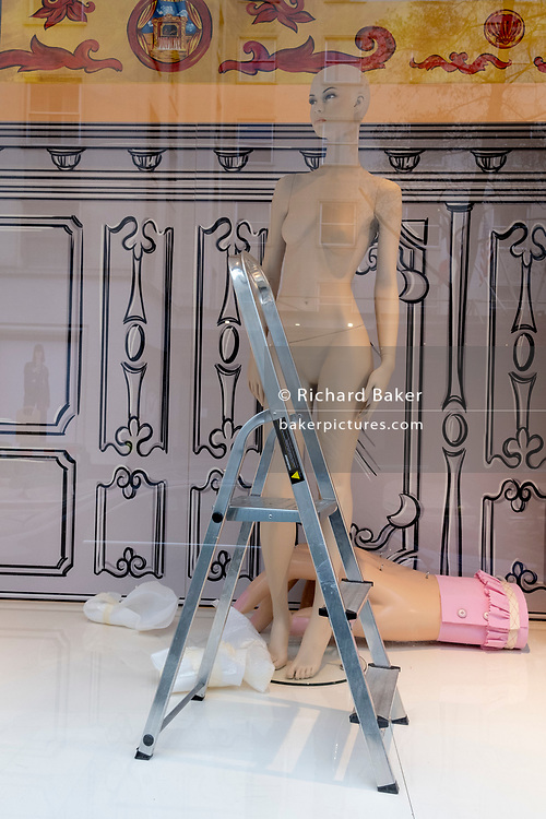 A female fashion mannequin stands unclothed next to stepladders in the window of the closed Conduit Street branch of Moschino in Mayfair during the third lockdown of the Coronavirus pandemic, on 4th March 2021, in London, England.