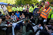 Protesters who have locked themselves together outside the drilling site run by Cuadrilla Resources, near Balcombe in South East England. Anti fracking protesters scuffled with police outside the gas exploration site.