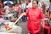 17 APRIL 2010 - BANGKOK, THAILAND: A Red Shirt fried banana vendor makes snacks for the Red Shirts. A whole economy has sprung up around the Red Shirt camp with vendors selling everything from snacks and meals to mats (that they sit on) to fans, hats and Red Shirt souvenirs. The Red Shirts continue to occupy Ratchaprasong Intersection an the high end shopping district of Bangkok. They are calling for Thai Prime Minister Abhisit Vejjajiva to step down and dissolve the parliament. Most of the Red Shirts support ousted former Prime Minister Thaksin Shinawatra.   PHOTO BY JACK KURTZ