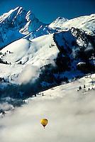 A hot air balloon floats over the Alps during International Hot Air Balloon Week, Chateau d'Oex, Switzerland