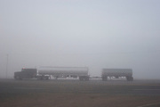 I the early morning mist a juggernaut passes a truck stop in Minot, North Dakota. These huge and powerful articulated trucks aree the life blood of America, transporting good in this case from Canada into the States along one of the busiest lengths of Interstate Highway in the US.