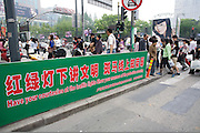 """A sign tells pedestrians to """"show thier manners"""" as they cross the street in an orderly fashion in central Shanghai. head of the Olympics, China is trying to improve its citizen's public manners and curb behavior that might offend foreigners"""