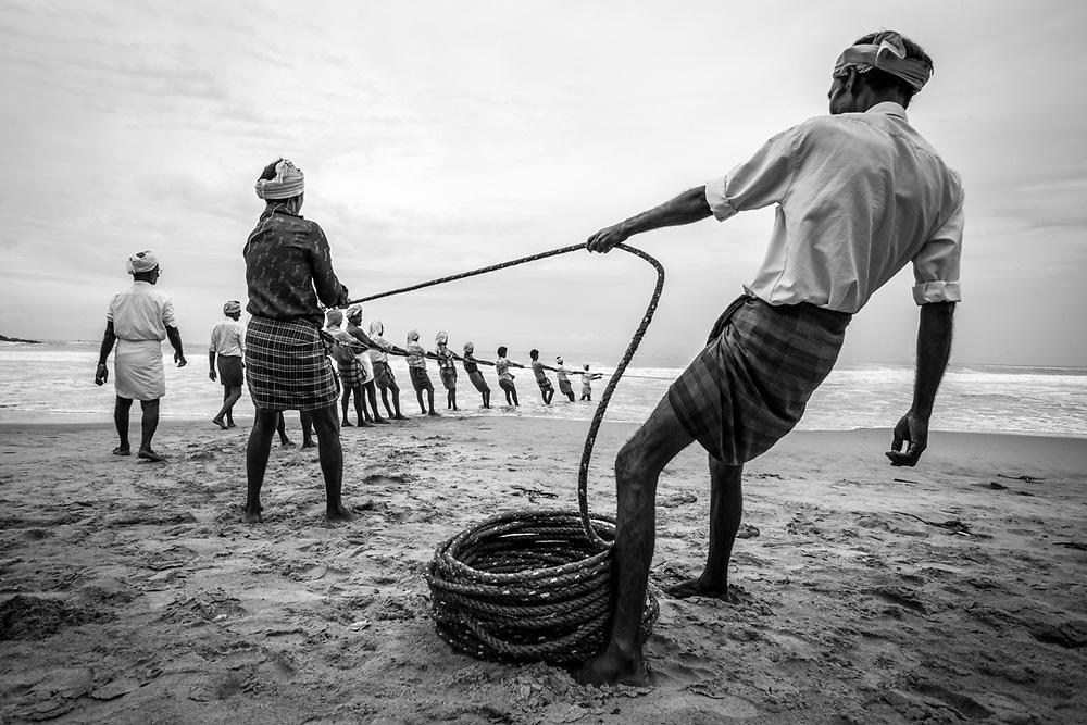 Kerala, India. A fishermen team from Kovalam is pulling toward the beach the fishing nets.<br /> Photo by Lorenz Berna