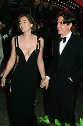 """Star of the film """"Four Weddings and a Funeral"""", Hugh Grant, arrives for the charity premiere with actress Elizabeth Hurley."""