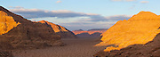 Sunset light on the sandstone cliffs rising above a high desert valley in Wadi Rum, Jordan.