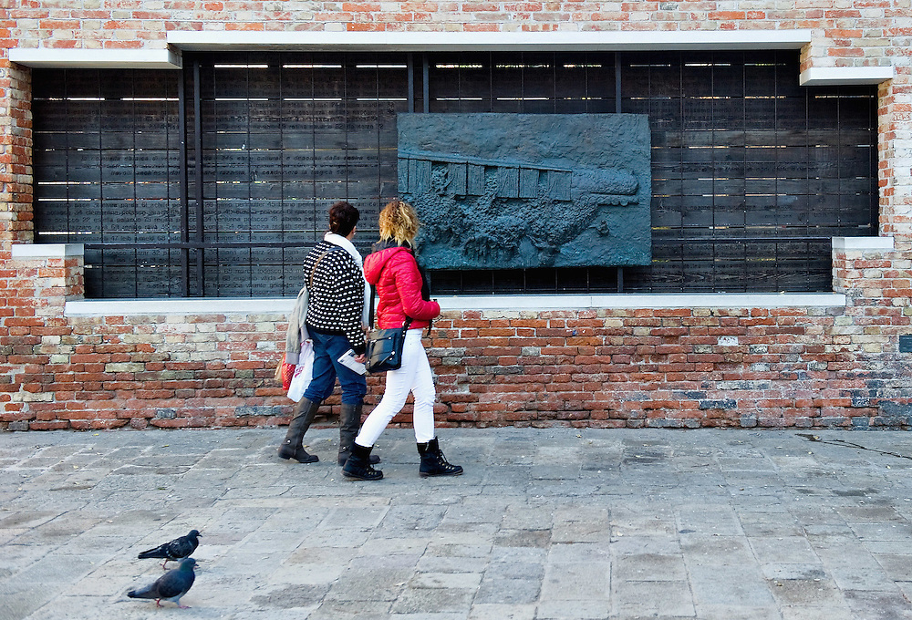 VENICE, ITALY - NOVEMBER 15: Two women walk in front of a monument remembering the holocaust at the Venice Ghetto on November 15, 2011 in Venice, Italy. Established in 1516 the Ghetto of Venice was the area were Jews were compelled to live during the Venetian Republic. The English term 'ghetto' is derived from the Venetian term for 'slag' and refers to the refuse left the foundry that was located on the same island. In present times the ghetto is a multi-ethnical area area seen as the cultural heart of the city, but with five synagogues remains the centre of the of Jewish community. .