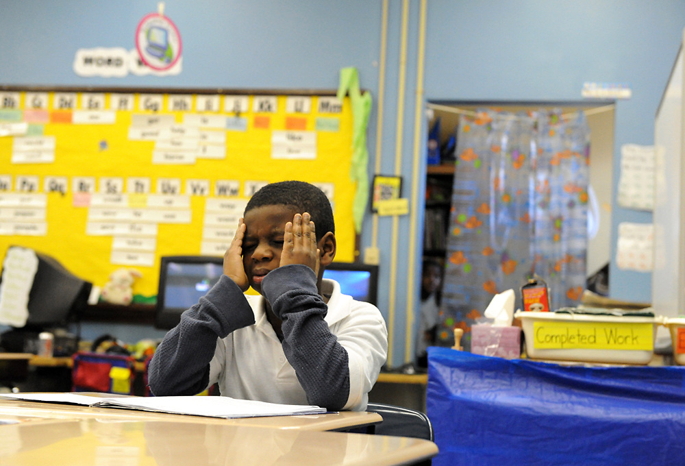 JaJuan tries to cope with a migraine during school.  His mother says his migraines increased in regularity after they started living in the shelter.