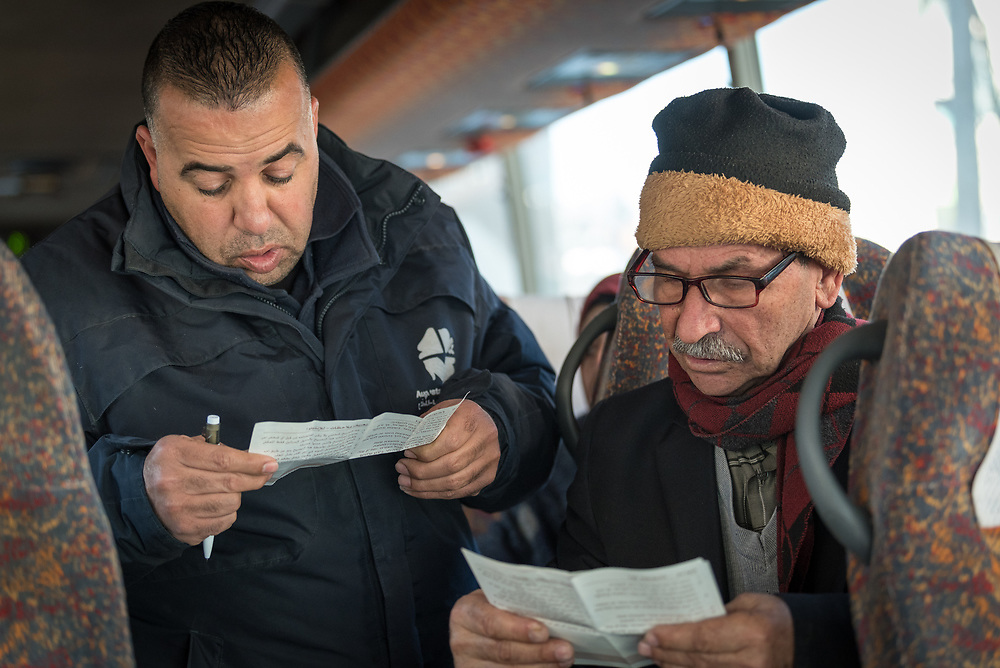 27 February 2020, Hebron: 68-year-old Nazer Muhtazar joins security staff Jad in reviewing paperwork, as he travels from Hebron to Jerusalem on a special bus offered by the Augusta Victoria Hospital in an effort to facilitate access to healthcare for patients living in the West Bank. Muhtazar travels on the bus once a week, and has been for the past seven months, for cancer treatment.