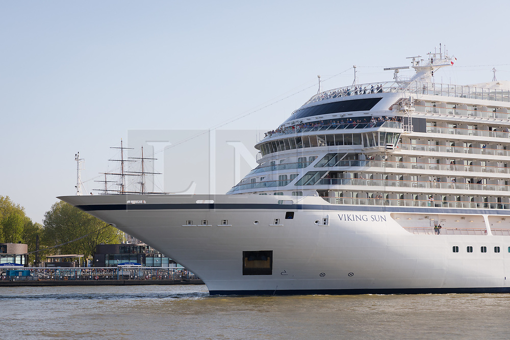 © Licensed to London News Pictures. 06/05/2018. London, UK.  228-metre-long cruise ship Viking Sun is seen making her way down the River Thames past the Cutty Sark at the end of a 3 day visit to Greenwich in south east London. The visit by Viking Sun, which has a capacity of 930 passengers, marks the beginning of London's cruise ship season. For passengers on board, London was the end of a 141 night round the world cruise which started in Miami last December. Photo credit: Vickie Flores/LNP