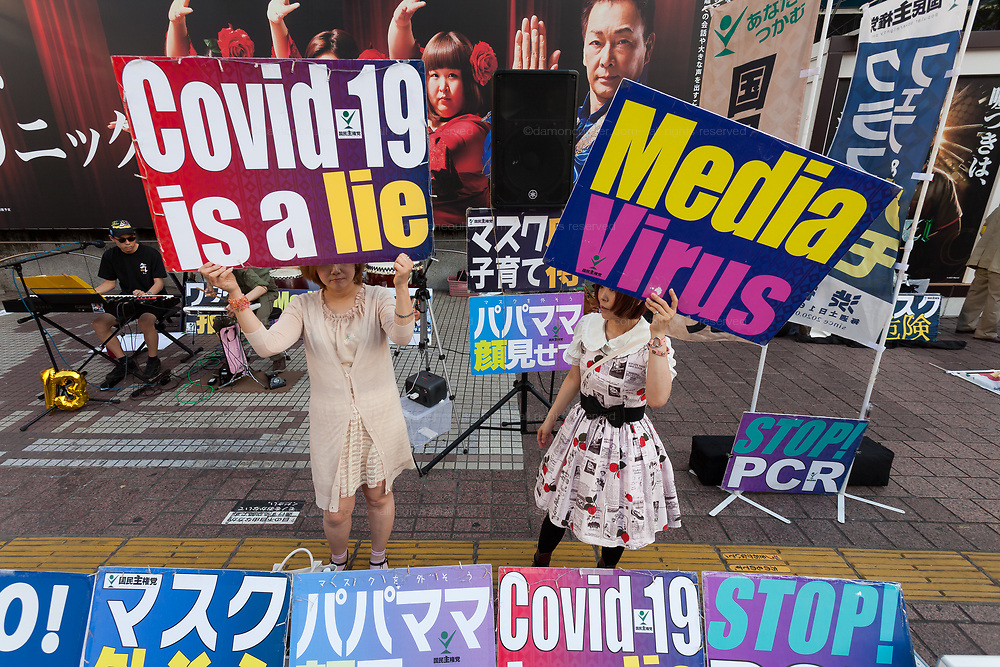 """Japanese women hold signs saying """"Covid-19 is a lie"""" and """"Media Virus"""" at a small demonstration against government and societal measures to combat the COVID19 pandemic  Shibuya, Tokyo, Japan. Saturday June 12th 2021. Supporters of Masayuki Hiratsuka of the Popular Sovereignty Party of Japan, who unsuccessfully ran for Tokyo Governor in 2020, held a music festival in the iconic Hachiko Square calling the Coronavirus pandemic a lie."""