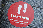 MERTHYR TYDFIL, WALES - 01 JUNE 2020 - 'Stand here' signs on the floor outside Lloyds Bank promoting social distancing while people use their cash machine.
