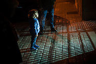 A migrant child waits at the door of the center of the red cross as the security guard lights up his face with the torch. Irun (Basque Country). January 03, 2019. A group of volunteers has created a host network to serve migrants and inform about the public services they are entitled to and the ways to cross the border. This group of volunteers is avoiding a serious humanitarian problem Irun, the Basque municipality on the border with Hendaye. As the number of migrants arriving on the coasts of southern Spain incresead, more and more migrants are heading north to the border city of Irun. One of the functions performed by these volunteers is to direct the newcomers to the centre the red cross has for migrants in transit, so that they can sleep in a safe place. (Gari Garaialde / Bostok Photo).