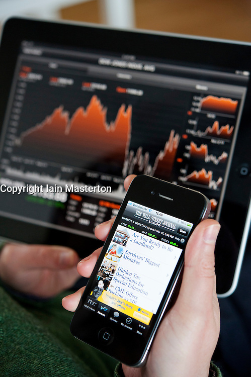 Woman using iPad tablet computer and iPhone  to check stock market prices of Dow Jones Industrial Average index