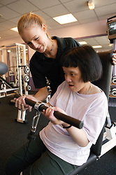 Access to services, Fitness instructor and disabled girl in the gym; using cable jungle,