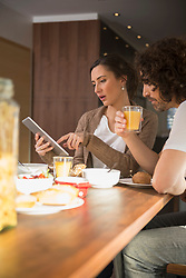 Mid adult woman using a digital tablet with her husband over breakfast, Munich, Bavaria, Germany