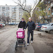 CAPTION: Parents Nina and Aleksander take their baby daughter Valentina for a walk near their flat in Volzhskiy, situated on the other side of the Volga River from Volgograd. LOCATION: Volzhskiy, Volgograd Oblast, Russia. INDIVIDUAL(S) PHOTOGRAPHED: Nina Panteleeyeva (left) and Aleksander Panteleeyev (right).