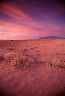 Sunset paints the Kelso Dunes area of the Mojave National Scenic Area with a warm glow in April 1994.  The area was included along with Death Valley and Joshua Tree national Monuments in the Desert Protection Act sponsored by California Senator Diane Feinstein.