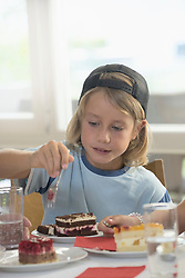 Boy Eating Cake at home, Eichenau, Bavaria, Germany