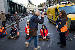 © Licensed to London News Pictures. 25/10/2021. London, UK. A member of the public begs Insulate Britain climate change activists to move as they block traffic on Bishopsgate in the City of London. The group have restarted their actions to block motorways and major roads causing disruption in the week before the COP26 climate meeting in Glasgow on 31/10/2021. Photo credit: Ben Cawthra/LNP