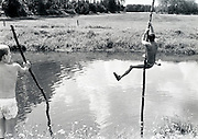 Boys playing in a pond with poles