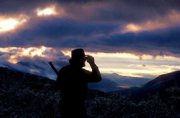 Stock photo of a hunter looking through binoculars over a mountain range