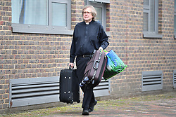 © Licensed to London News Pictures. 24/06/2017. London, UK. A vicar carries bags from a flat as Residents are evacuated from the Dorney block on the Chalcots Estate in Camden after it failed a fire inspection because of combustable cladding. More than 700 flats in tower blocks on an estate in the Swiss Cottage area of north-west London are being evacuated because of fire safety concerns. Photo credit: Ben Cawthra/LNP