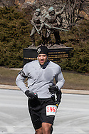 """KEVIN WILKINS of New WIndsor, New York runs up a  hill during the West Point Half-Marathon Fallen Comrades Run at the United States Military Academy in West Point, New York. The monument """"To the American Soldier"""" is in the background. The nine-foot bronze statue was sculpted by Felix de Weldon, who also did the Iwo Jima Statue at Arlington National Cemetery."""