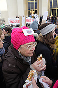 January, 21st, 2017 - Paris, Ile-de-France, France: Woman eating with 'Paris against Trump' badge. Thousands of protesters in Paris join anti-Trump Women's March around the world.